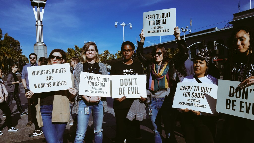 A photo of attendees at the Google walkout, carrying signs like 'Don't Be Evil'