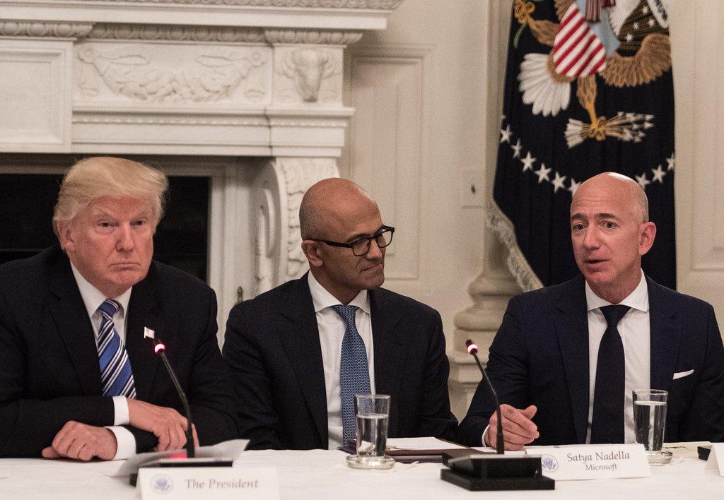 Amazon's Bezos and Microsoft's Nadella sit at Trump's table.