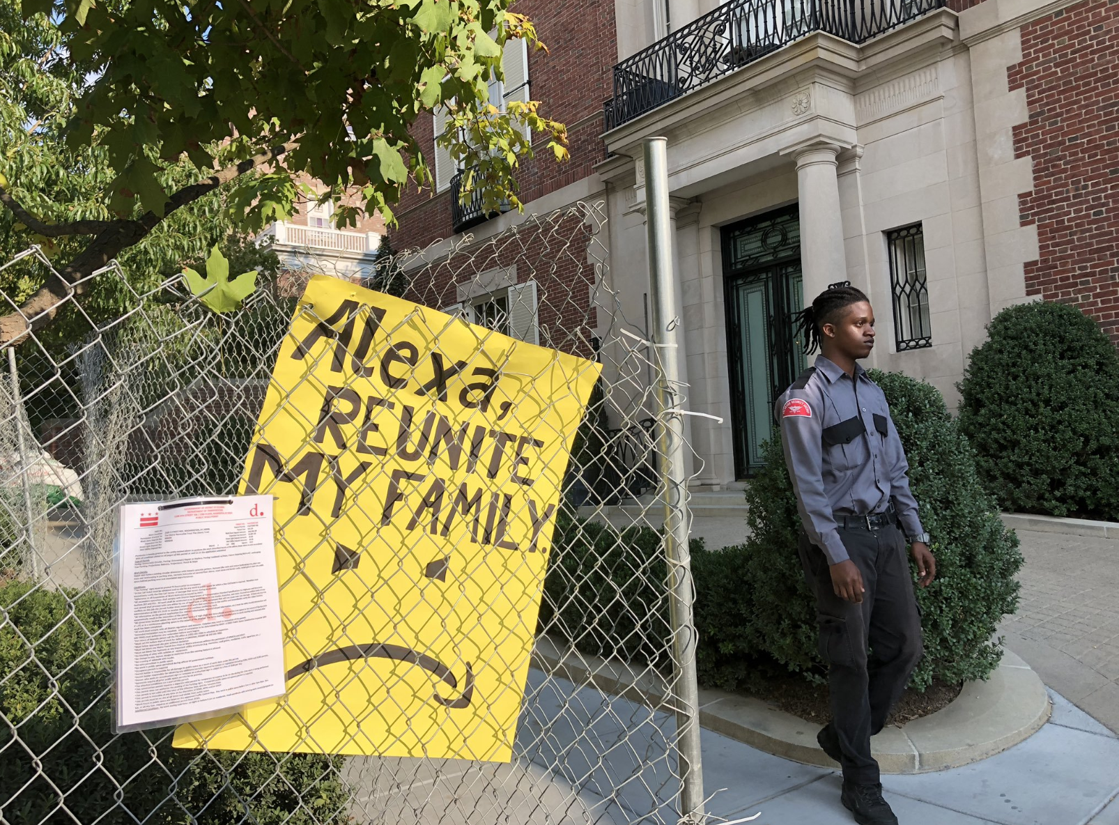 A poster on a fence reading 'Alexa, reunite my family'