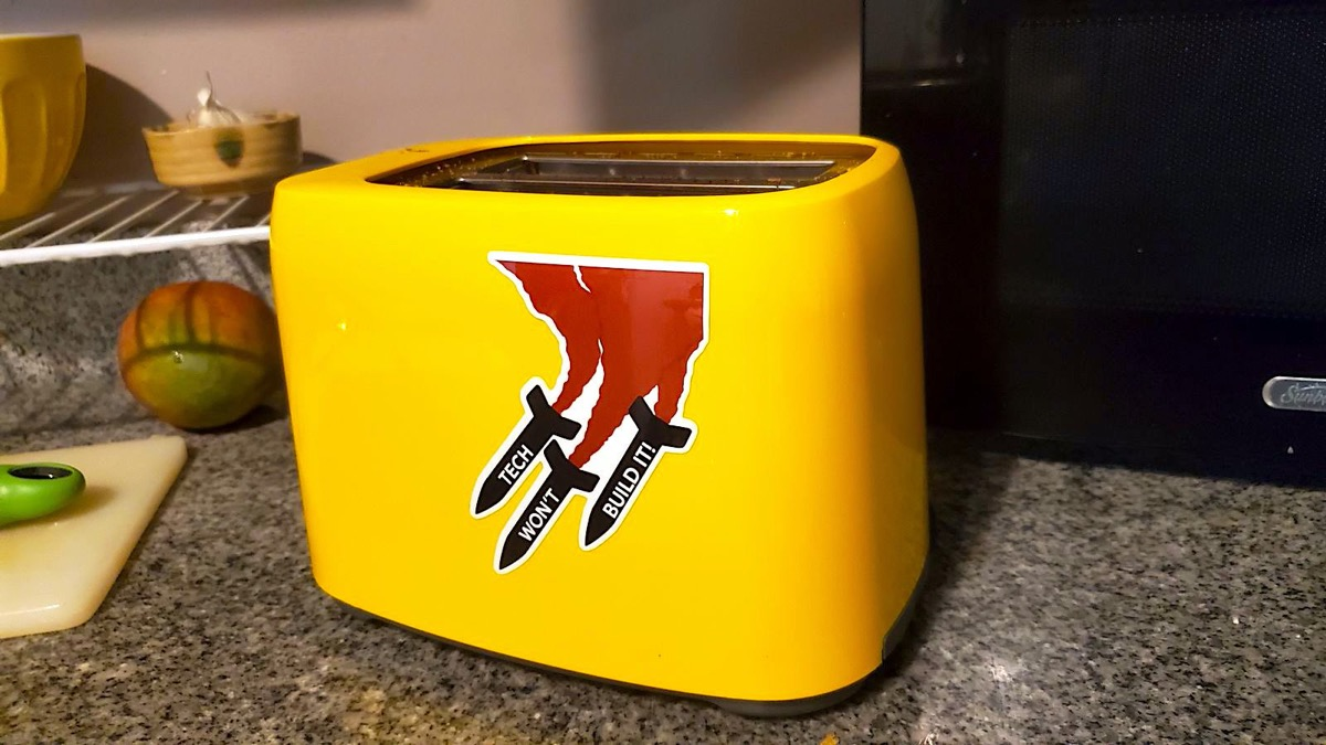 A yellow toaster with a sticker that says Tech Won't Build It