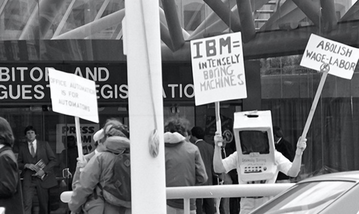 Image of people in front of the entrance to a convention center, one wearing a computer costume and holding a placard that reads IMB = intensely boring machines.