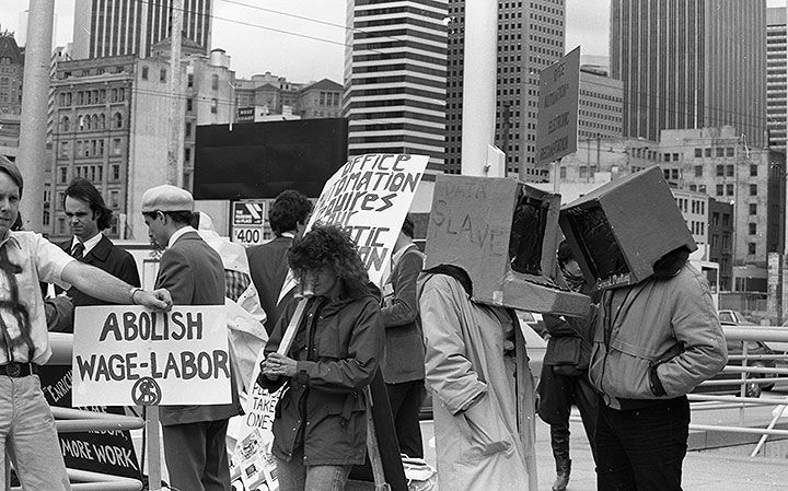 Image of people in front of the entrance to a convention center with skyscrapers in the background and holding placards that read ABOLISH WAGE-LABOR AND OFFICE AUTOMATION REQUIRES OUR... two people are wearing computer costumes on their head, one with the word DATA SLAVE written on the side.