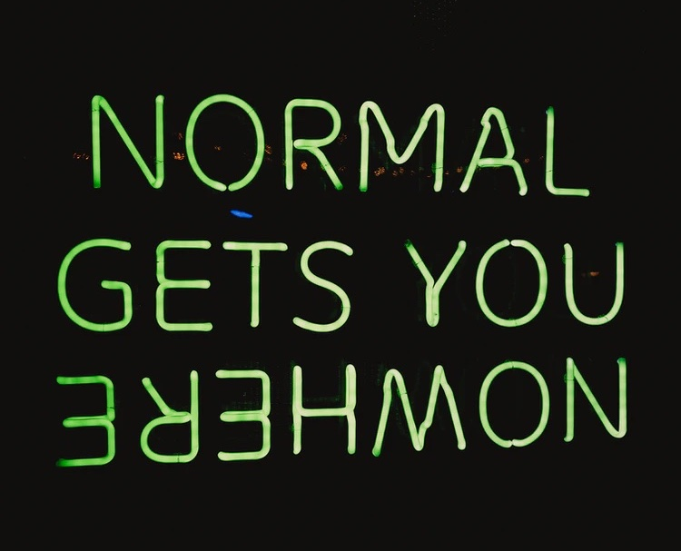 A neon green sign on a black background that says NORMAL GETS YOU NOWHERE, with NOWHERE upside down and backwards