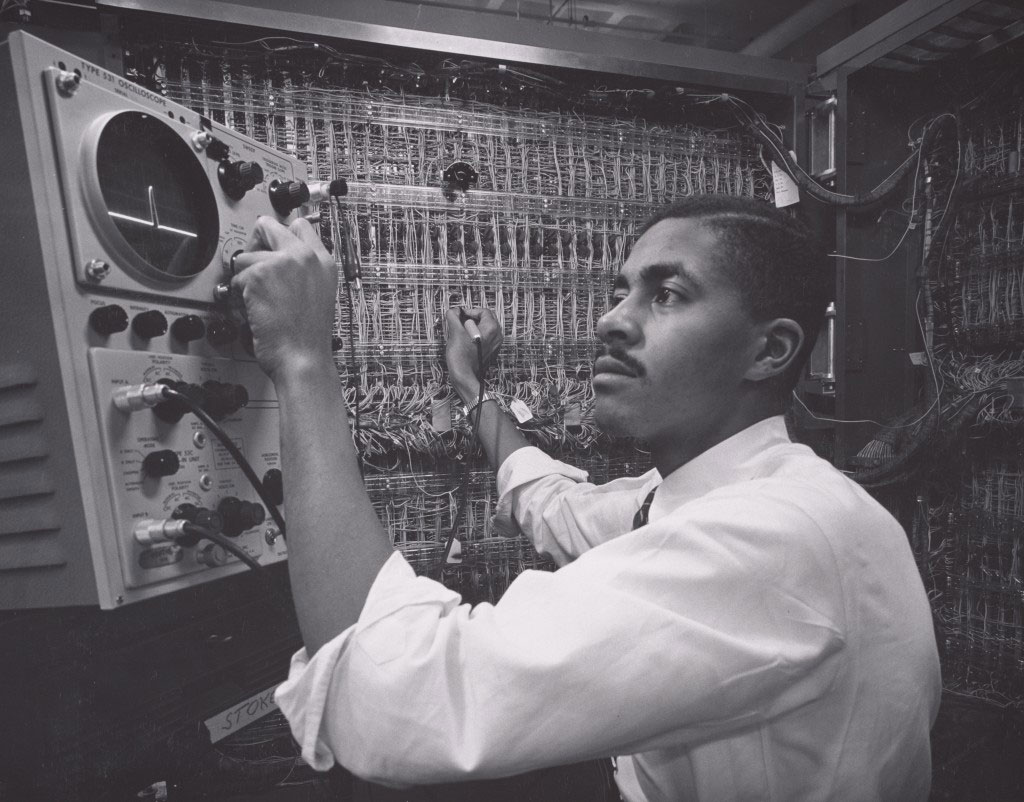A Black engineer seated at an IBM mainframe, 1956