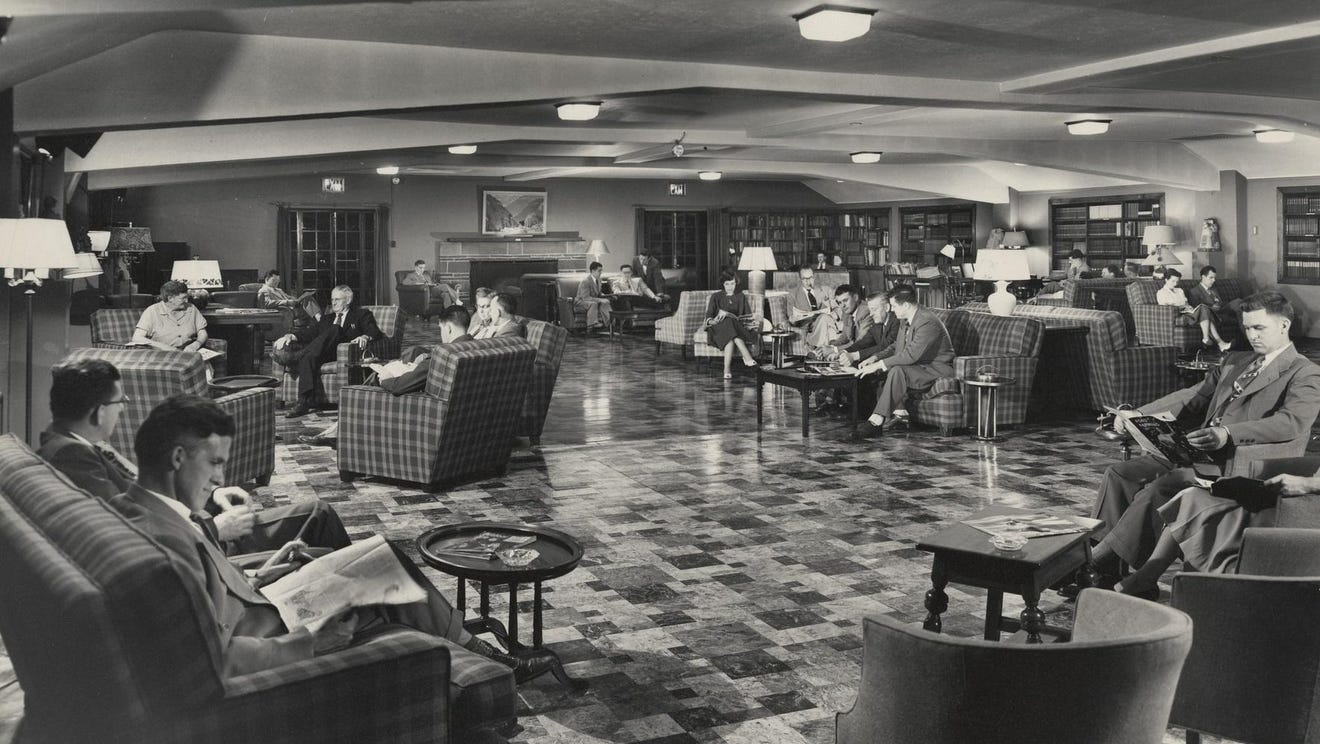 Black-and-white photograph of a large, fancy-looking room with about a dozen people sitting in sofas, reading newspapers and talking. Most of the people depicted are men wearing suits, though there are a few women present.