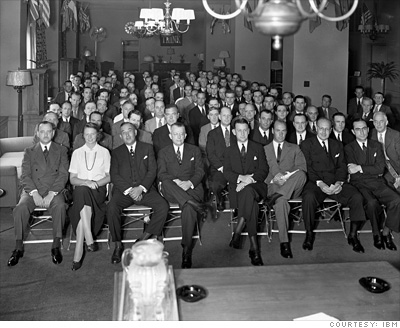 Black-and-white photograph showing a seated audience, most of whom are men wearing suits.