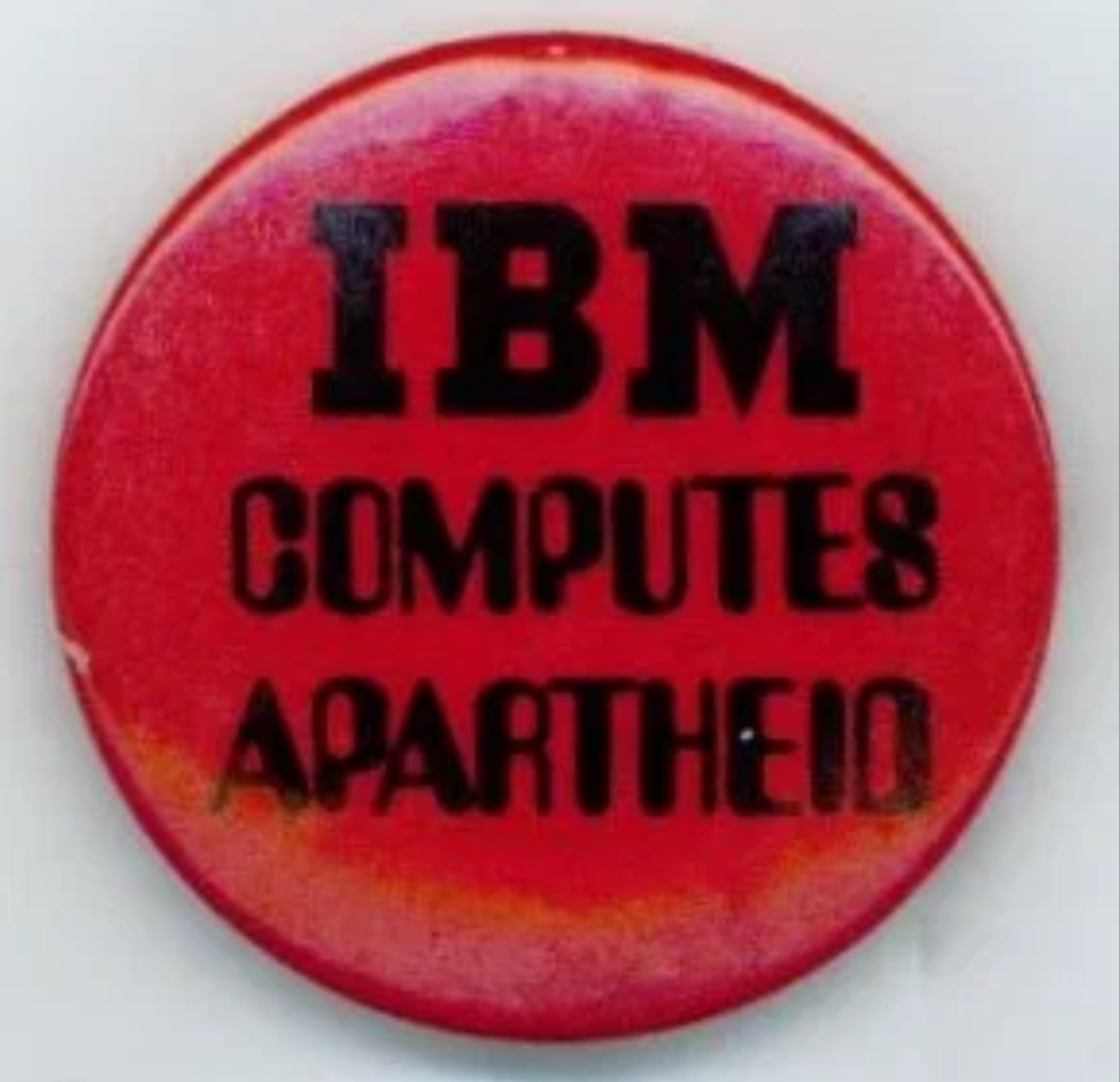 Photo of a red button that reads 'IBM COMPUTES APARTHEID'