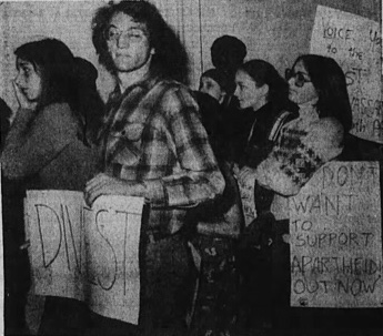 Black-and-white photograph of protesters carrying anti-apartheid signs, including a bespectacled man holding up a sign that says 'DIVEST'