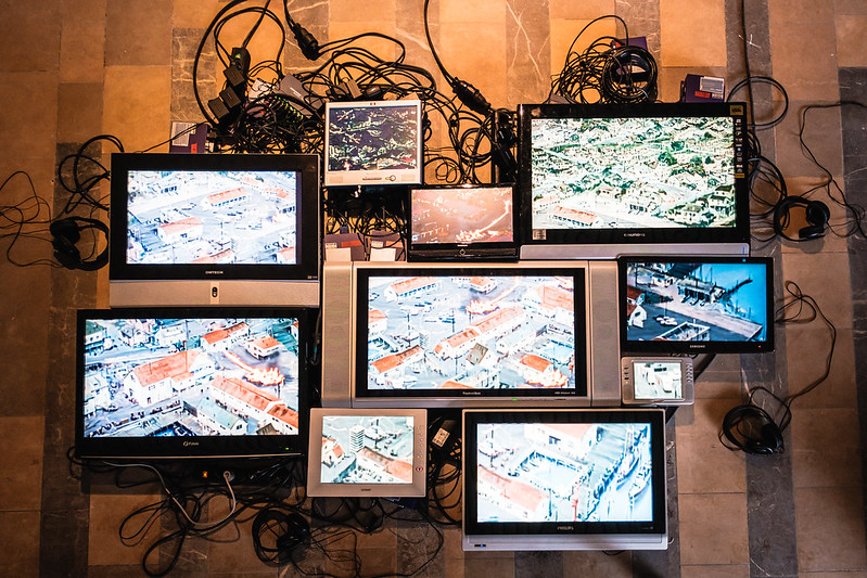Several screens are assembled into an art installation, showing images of buildings and piers, with tangled wires visible in the background.